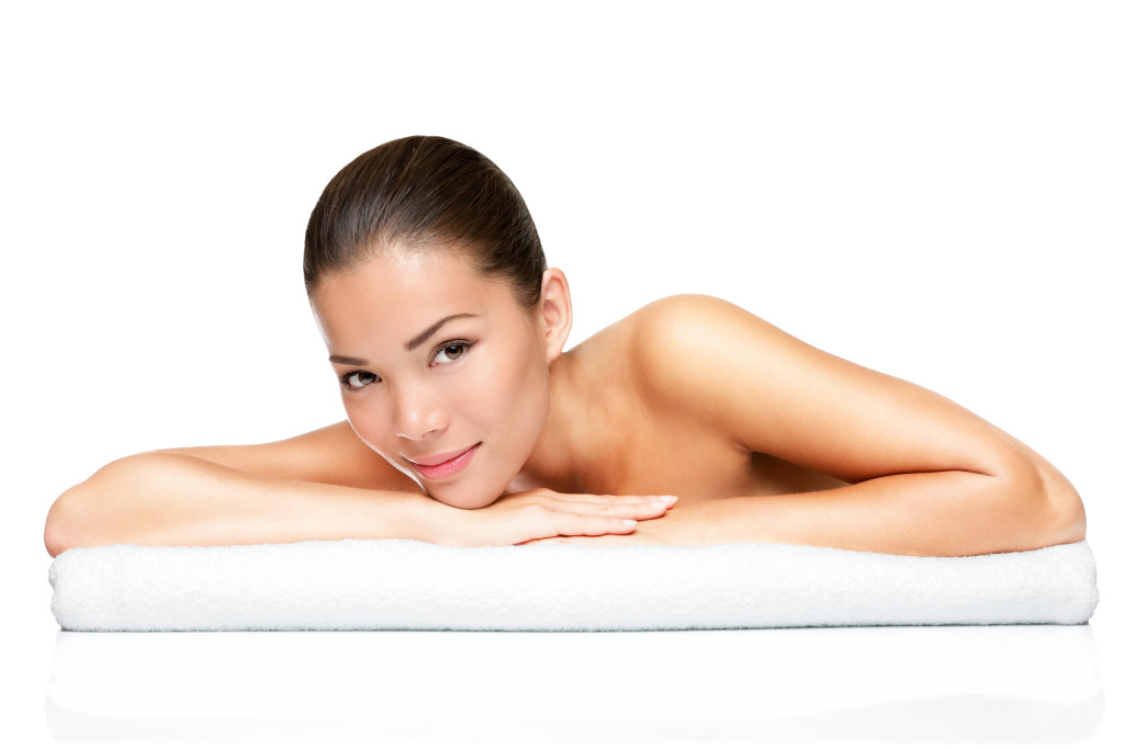 Spa beauty skin treatment woman on white towel. Gorgeous beutiful multiracial Caucasian / Asian female model with perfect skin lying on towel having beauty treatment at spa. Young woman in her 20s isolated on white background.